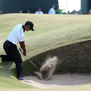 Tiger Woods plays out of a bunker on the 12th hole during the first round of the 142nd Open Championship at Muirfield.