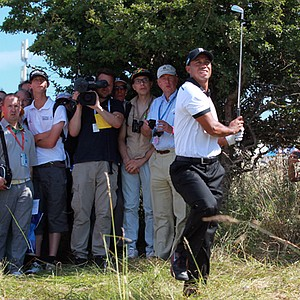 Tiger Woods had to take an unplayable lie after sending his tee ball into the long rough to the left of the first fairway. His third shot -- shown here -- found a right, greenside bunker. He got up-and-down to save bogey at the Open Championship.