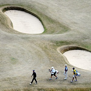 Dustin Johnson and Nicolas Colsaerts walk up the 10th hole during the first round of the Open Championship at Muirfield.