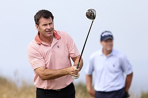 Nick Faldo watches his shot as Tom Watson looks on during the first round of the 2013 Open Championship at Muirfield.