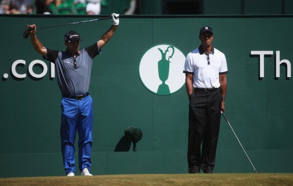 Graeme McDowell and Tiger Woods look on from the first tee during the first round of the 142nd Open Championship at Muirfield.