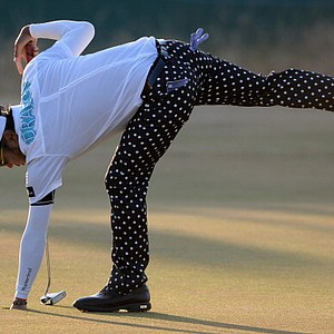 Shingo Katayama retrieves his ball on the 18th green during the second round of the Open Championship.
