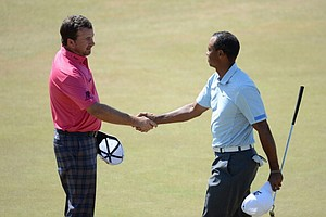 Graeme McDowell shakes hands with Tiger Woods on the 18th green during the second round of the Open Championship at Muirfield.