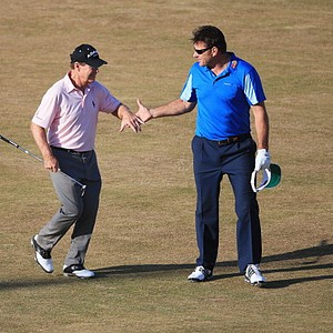 Tom Watson and Sir Nick Faldo shake hands as they walk down the 18th fairway during the second round of the  Open Championship.