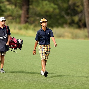 Shuai Ming Wong, 13, one of the youngest players, walks with his caddie Frankie Capan up the 11th fairway during the 66th U. S. Junior Amateur Championship at Martis Camp Club.