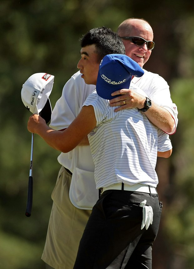 Caddie Mike Lewis congratulates his player, Doug Ghim after defeating Adam Wood, 2 and 1, during the Round of 64 at the 66th U. S. Junior Amateur.