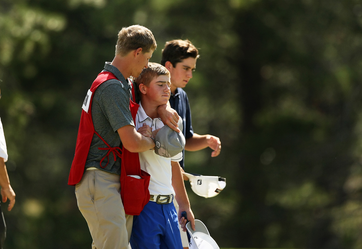 John Augenstein is consoled by his caddie Michael Coon after losing to Davis Riley 4 and 3 during the semifinals at the 66th U. S. Junior Amateur.