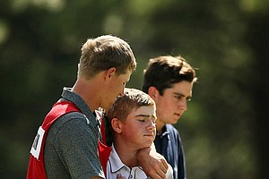 John Augenstein is consoled by his caddie Michael Coon after losing to Davis Riley 4 and 3 during the semifinals at the 66th U. S. Junior Amateur Championship.