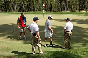 Davis Riley talks with referee Skip Gist, after calling a penalty on himself on the 34th hole, during the finals of the 66th U. S. Junior Amateur Championship at Martis Camp Club. At left is assistant referee Peter Castleman and Riley's caddie Christiano DiPasquale.