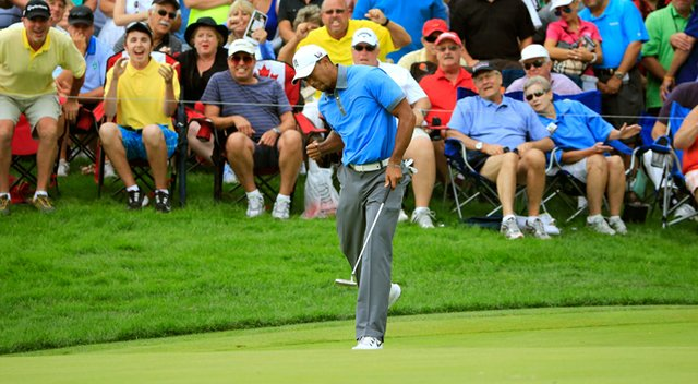 Tiger Woods reacts as he makes a birdie putt on the 12th green during the second round of the WGC-Bridgestone Invitational at Firestone Country Club in Akron, Ohio.