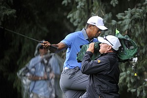 Tiger Woods trips over a TV cameraman during the second round of the 2013 WGC-Bridgestone Invitational at Firestone CC in Akron, Ohio.