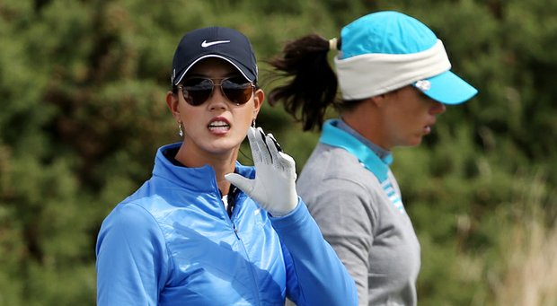 Michelle Wie and Karine Icher walk in after weather brought an early end to the third round of the 2013 Women's British Open at St. Andrews.