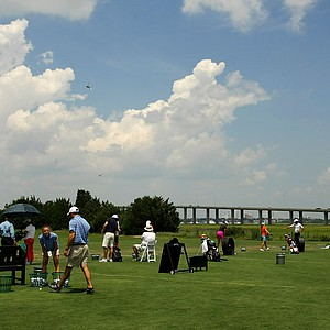 Players hit the range with a view of the James Island connector during a practice round prior to the 2013 U. S. Women's Amateur at Country Club of Charleston.