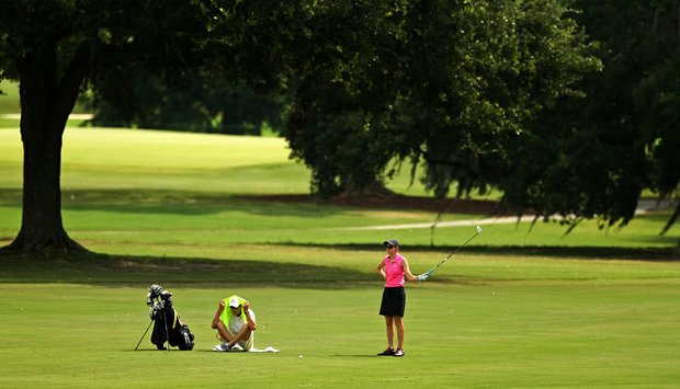 Spencer Heller, right, waits to hit at No. 18 as her caddie/boyfriend, Steven Warne, tries to keep cool during a practice round prior to the 2013 U. S. Women's Amateur at Country Club of Charleston.