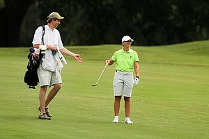 Liz Waynick hands her caddie, Thomas Ford, a club during the first round of stroke play at the 2013 U. S. Women's Amateur at Country Club of Charleston.