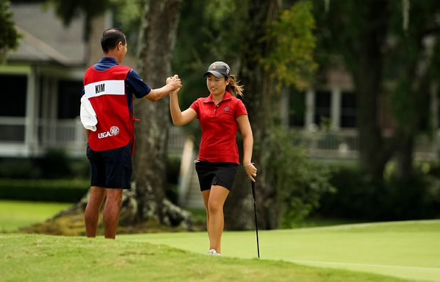 Kyung Kim high-fives her caddie/dad, Doug, after making a long putt at No. 8 during the first round of stroke play at the 2013 U. S. Women's Amateur at Country Club of Charleston.