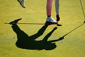 A player is silhouetted on the practice green during the first round of stroke play at the 2013 U. S. Women's Amateur at Country Club of Charleston.