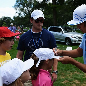Rickie Fowler signs his autograph for fans during a practice round prior to the start of the 95th PGA Championship at Oak Hill Country Club.