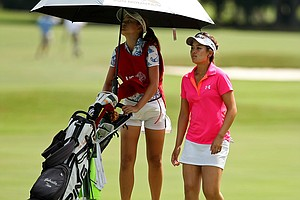 Gabriella Then walks up No. 18 as her sister/caddie Angella jumps to see her ball on the putting service during the second round of stroke play at the 2013 U. S. Women's Amateur.