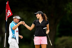 Emily Tubert gets a fist bump from her caddie Lorcan Morris during the second round of stroke play at the 2013 U. S. Women's Amateur at Country Club of Charleston. Morris is the caddie for LPGA's Ryann O'Toole.