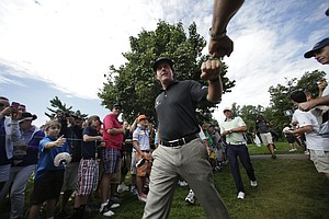 Phil Mickelson taps fists with a fan as he walks to the ninth tee during a practice round for the PGA Championship at Oak Hill Country Club.