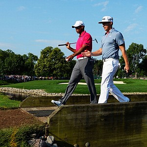 Tiger Woods and Hunter Mahan cross a bridge during a practice round before the PGA Championship at Oak Hill Country Club.