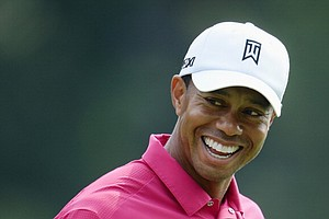 Tiger Woods smiles during a practice round prior to the start of the 95th PGA Championship at Oak Hill Country Club.