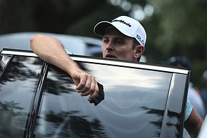 Justin Rose evacuates the course after play was suspended due to inclement weather during the first round.