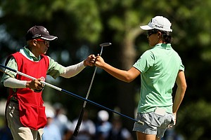 Yueer Cindy Feng gets a fist bump from her dad/caddie Delin during the quarterfinals of match play at the 2013 U. S. Women's Amateur at Country Club of Charleston. Feng will meet Doris Chen for the semifinals.