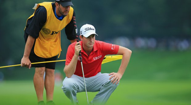 Webb Simpson lines up a putt with his caddie Paul Tesori on the eighth green during the second round of the 95th PGA Championship.