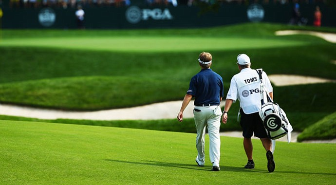 David Toms walks with his caddie Scott Gneiser to the 18th green during the first round of the 95th PGA Championship in Rochester, N.Y.