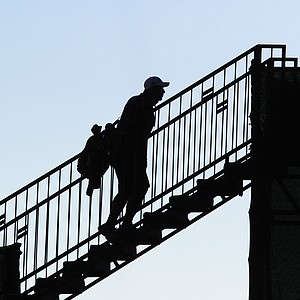 An unidentified caddie heads for a bridge to the first tee during the 2013 PGA Championship at Oak Hill.