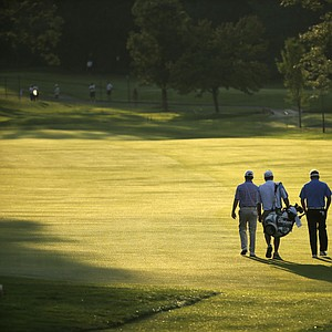 David Toms and Carl Pettersson walk with their caddies during Wednesday practice for the 2013 PGA Championship at Oak Hill.