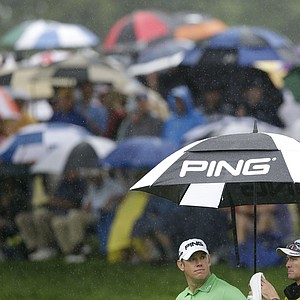 Lee Westwood gets an assist in the rain from his caddie during the 2013 PGA Championship at Oak Hill.