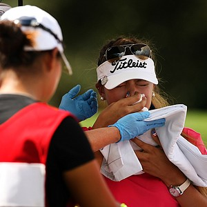 Alison Lee sits in a medics cart having her nosebleed tended to at No. 4 during the semifinals of match play at the 2013 U. S. Women's Amateur at Country Club of Charleston.