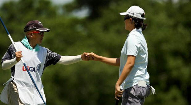 Yueer Cindy Feng gets a fist bump from dad and caddie Delin Feng.