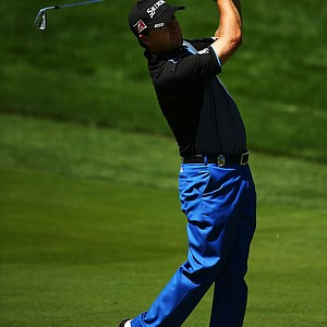 Graeme McDowell watches his approach shot on the first hole during the third round of the 95th PGA Championship.