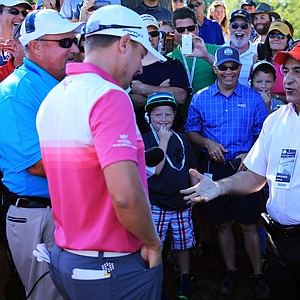 Jonas Blixt talks with Muhammad Khokhar of Rochester, N.Y., after a wayward tee shot landed in Khokar's pocket on the 18th hole during the third round of the PGA Championship.