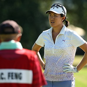 Yueer Cindy Feng and her dad/caddie, Delin, talk before leaving the 11th green during the final round of match play at the 2013 U. S. Women's Amateur at Country Club of Charleston.