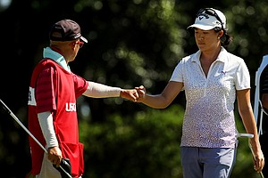 Yueer Cindy Feng fist bumps with her dad/caddie, Delin, at No. 13 during the first 18 of the final round of match play at the 2013 U. S. Women's Amateur at Country Club of Charleston.