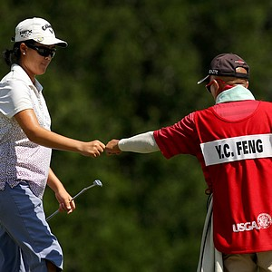 Yueer Cindy Feng gets a fist bump from her dad, Delin, at No. 13, the 31st hole, during the final round of match play at the 2013 U. S. Women's Amateur at Country Club of Charleston.