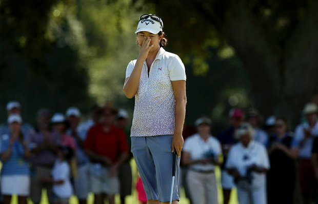 Yueer Cindy Feng covers her face as she misses her putt at No. 17, the 35th hole, during the final round of match play at the 2013 U. S. Women's Amateur at Country Club of Charleston.