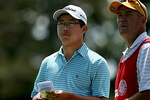 Jim Liu with his caddie Sean Fleming lost to Chelso Barrett during the Round of 64 at the 2013 U. S. Amateur at The Country Club.
