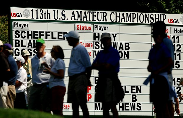 Spectators watch tee shots near the scoreboard at No. 13 during the Round of 32 at the 2013 U. S. Amateur at The Country Club.
