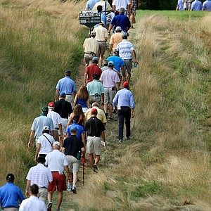 Spectators make their way down the 13th fairway during the Round of 16 at the 2013 U. S. Amateur at The Country Club.