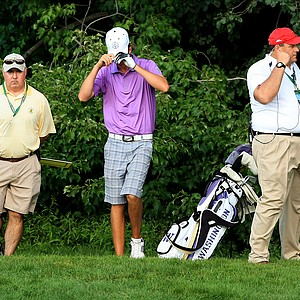 Charlie Hughes pulls his hat down over his eyes after finally finding his ball in the woods at No. 15 during the Round of 16 at the 2013 U. S. Amateur at The Country Club.