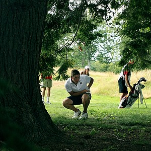 Brandon Matthews bends down to look through the trees to see where his shot ended up at no 14 during the quarterfinals at the 2013 U. S. Amateur at The Country Club. He carded a 7 on that hole.