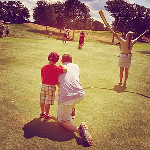 Chris Ryan and his son Max watch Neil Raymond hit a shot at No. 13 during the quarterfinals at the 2013 U. S. Amateur at The Country Club.