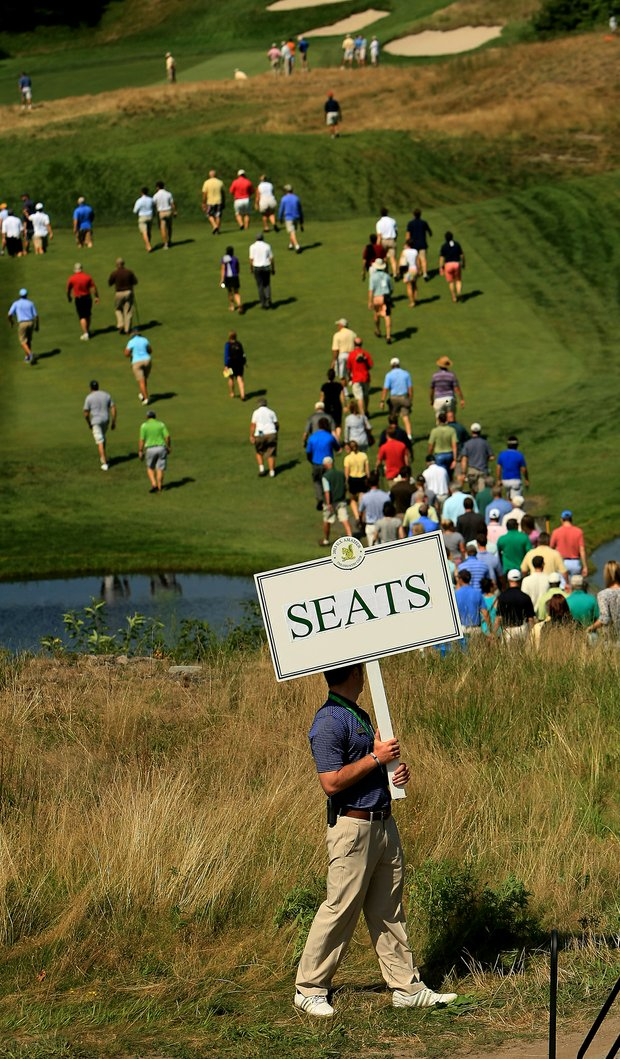 A volunteer with a seat sign during the semifinals at the 2013 U. S. Amateur at The Country Club.