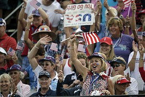 Golf fans cheer from the bleachers on the first tee at the start of a foursome match in the Solheim Cup.